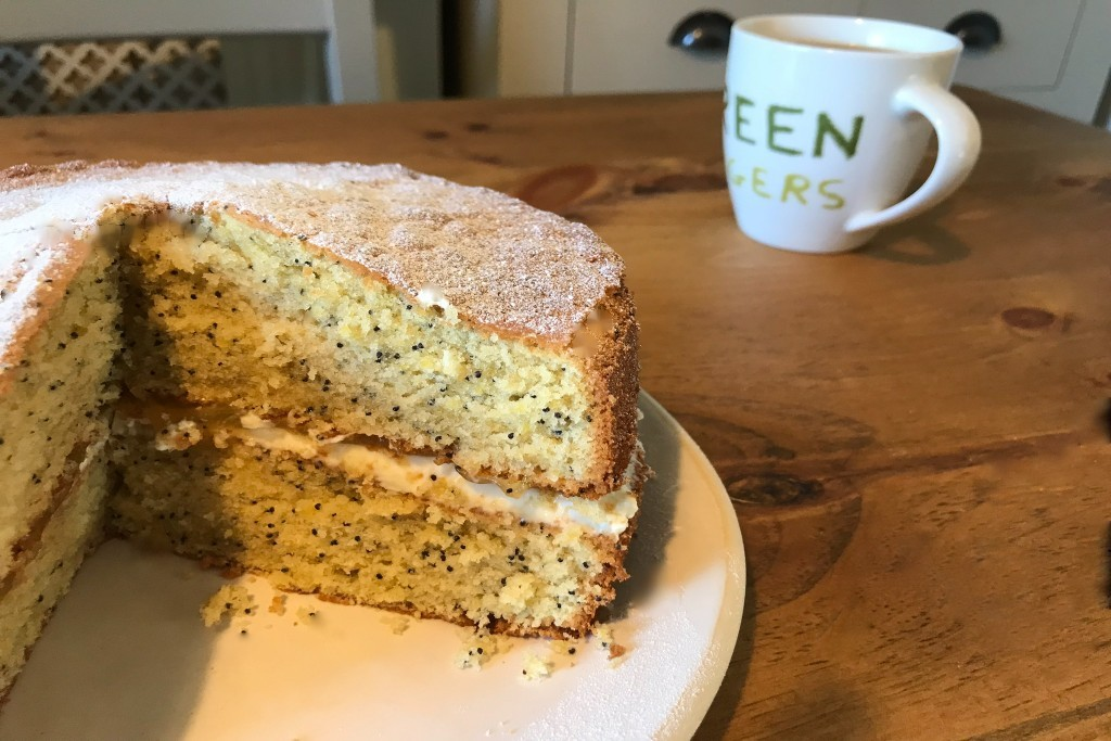 A Lemon and Poppy Seed cake with a slice taken out, sitting next to a cup of tea.