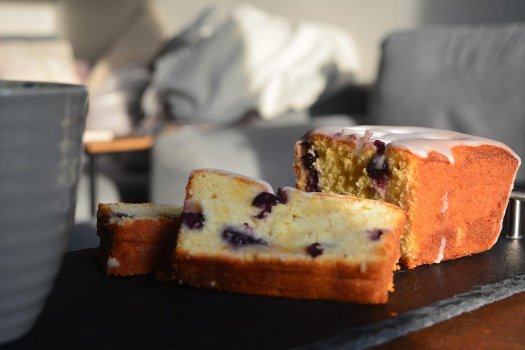 Lemon and Blueberry loaf cake on a slate serving tray with a mug of coffee.